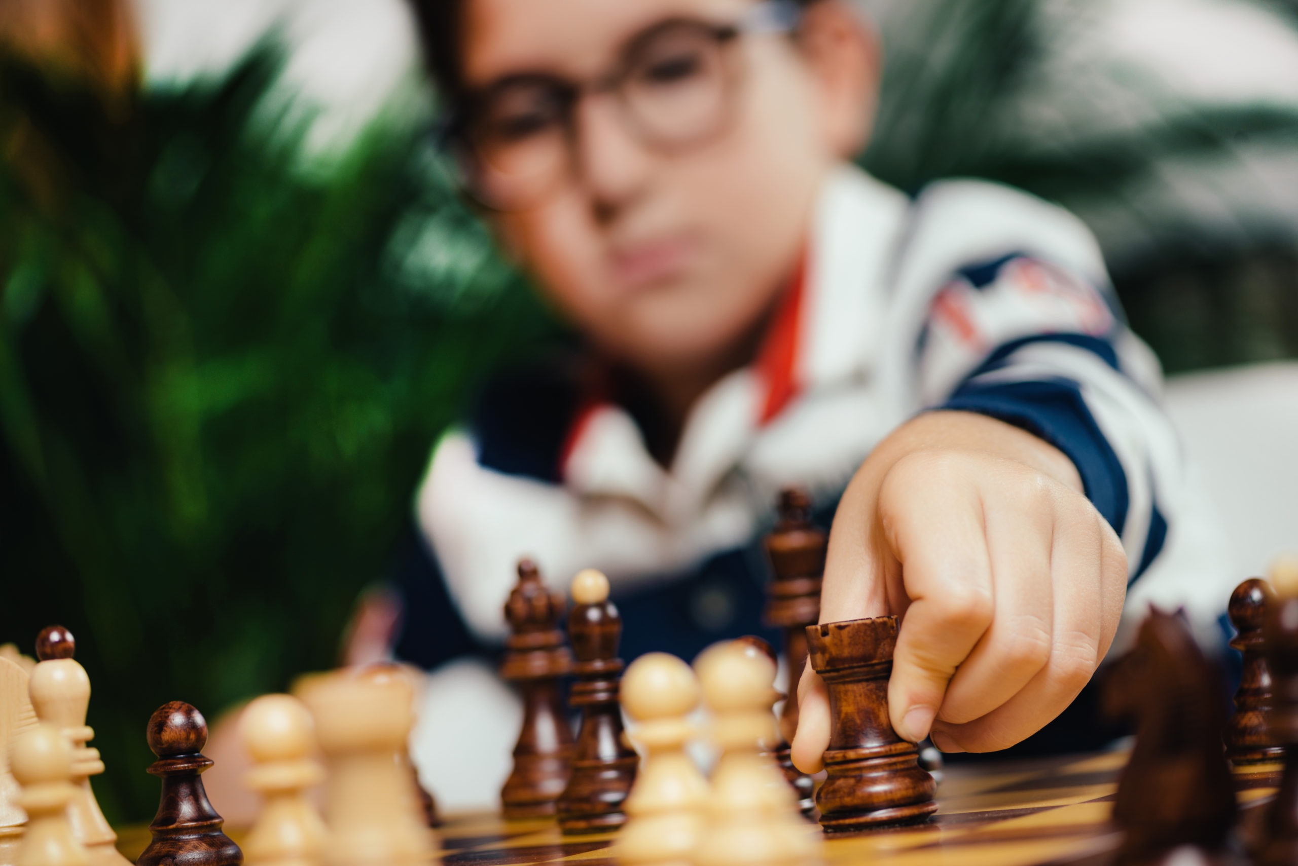 Boy playing chess at home. Sitting at the table and thinking hard.