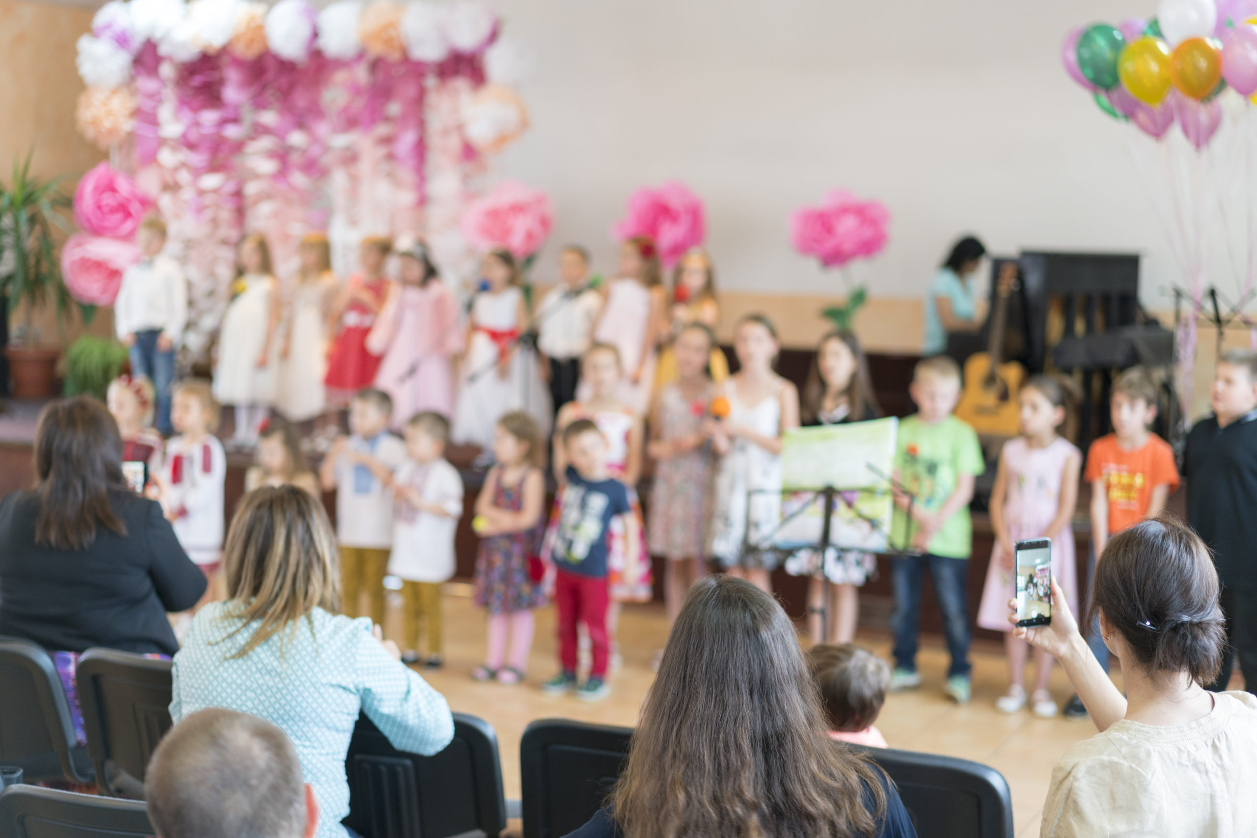 Children's party in primary school. Young children on stage in kindergarten appear in front parents. blurry.