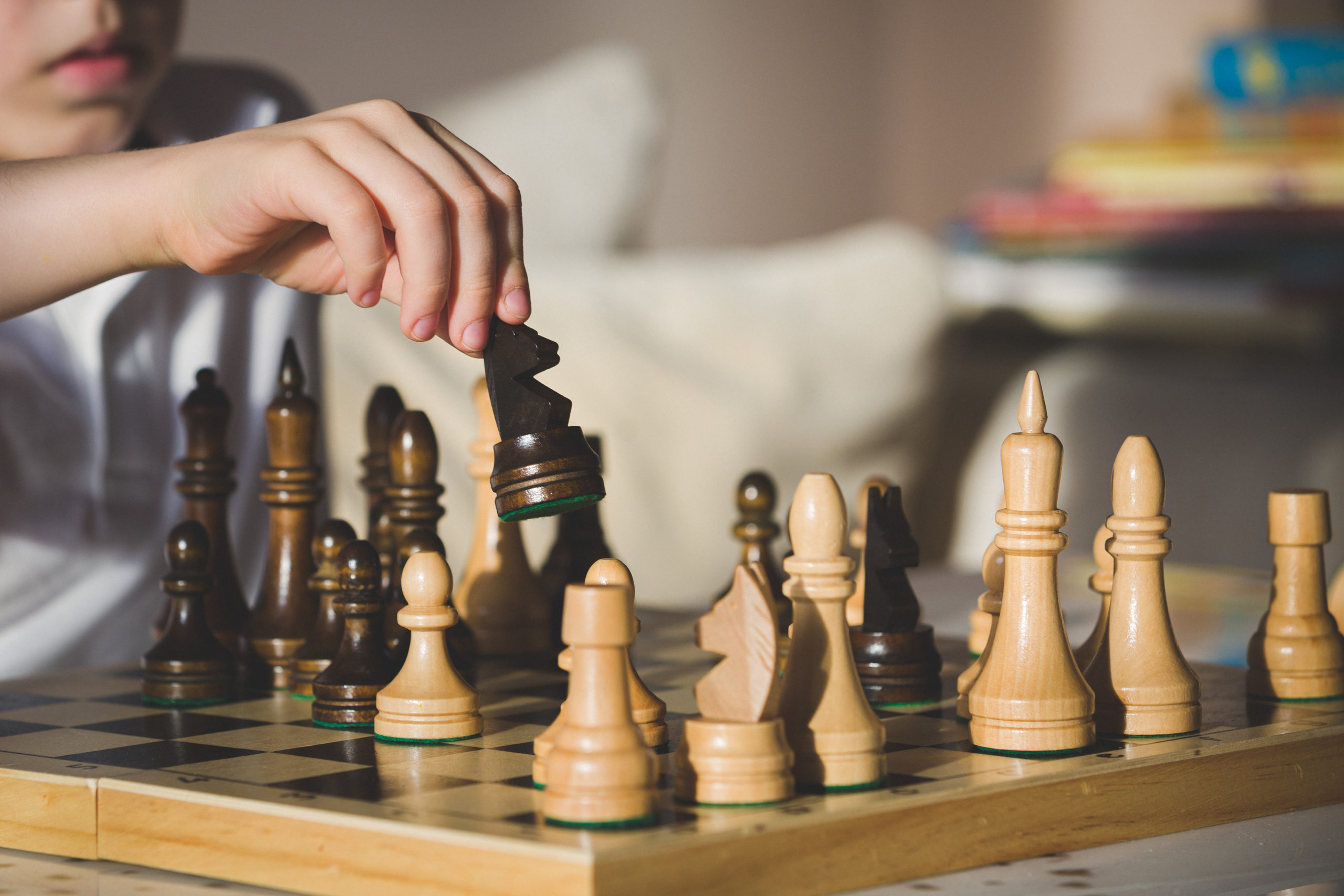 A cute boy with a serious look sits at a table and plays chess. The kid picked up the chess piece of the horse and makes his move. Early development, home educational games for children