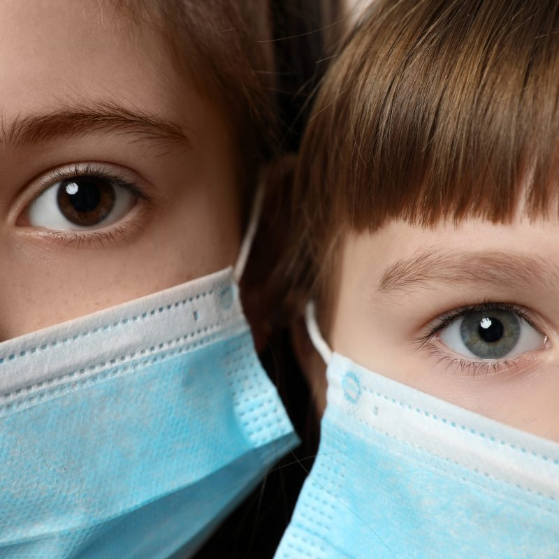 Little girls in medical masks, closeup. Virus protection